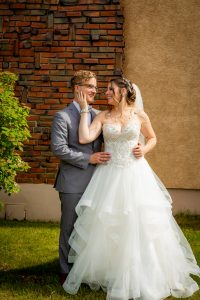 bride and groom outside brick wall
