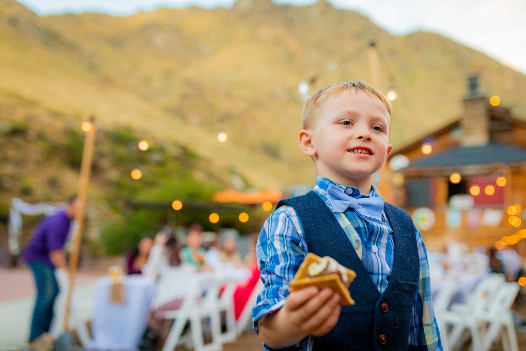 Boy holding smore at wedding reception in Colorado.