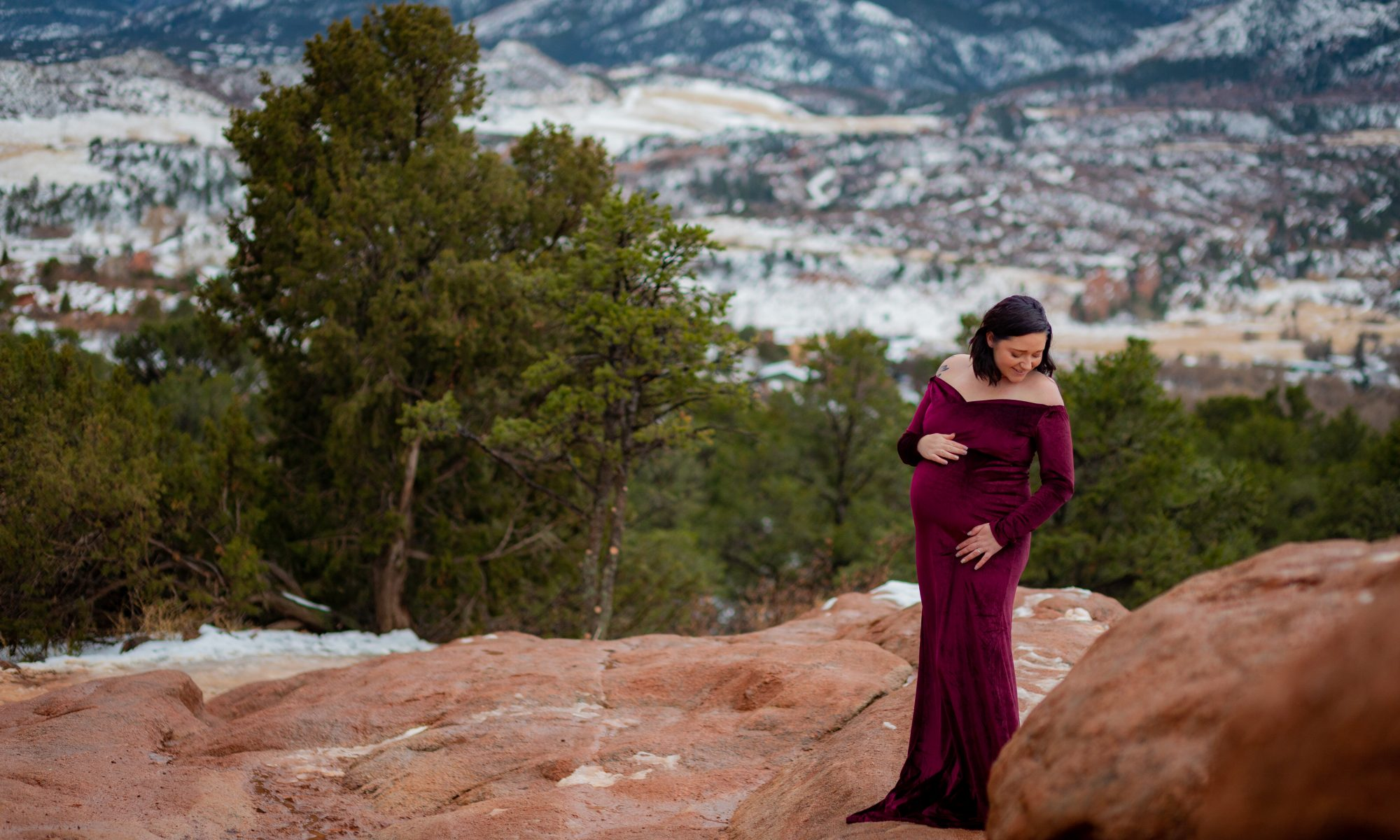 Maternity Portrait in the snow at Garden of the Gods park in a red gown