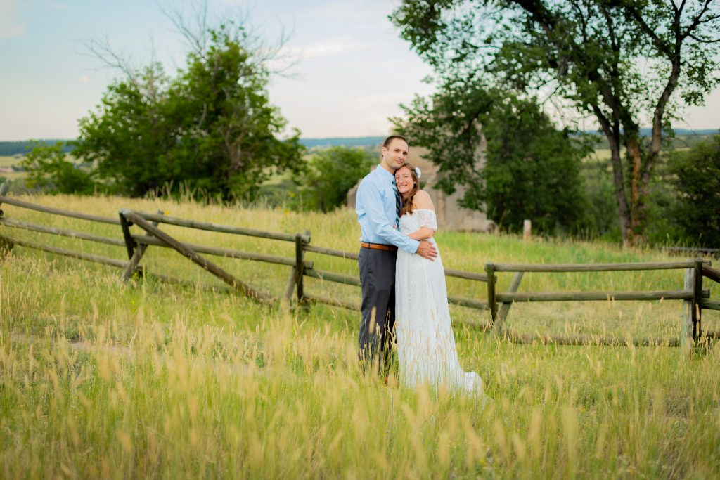 Couple standing in front of homestead at Castlewood Canyon State Park