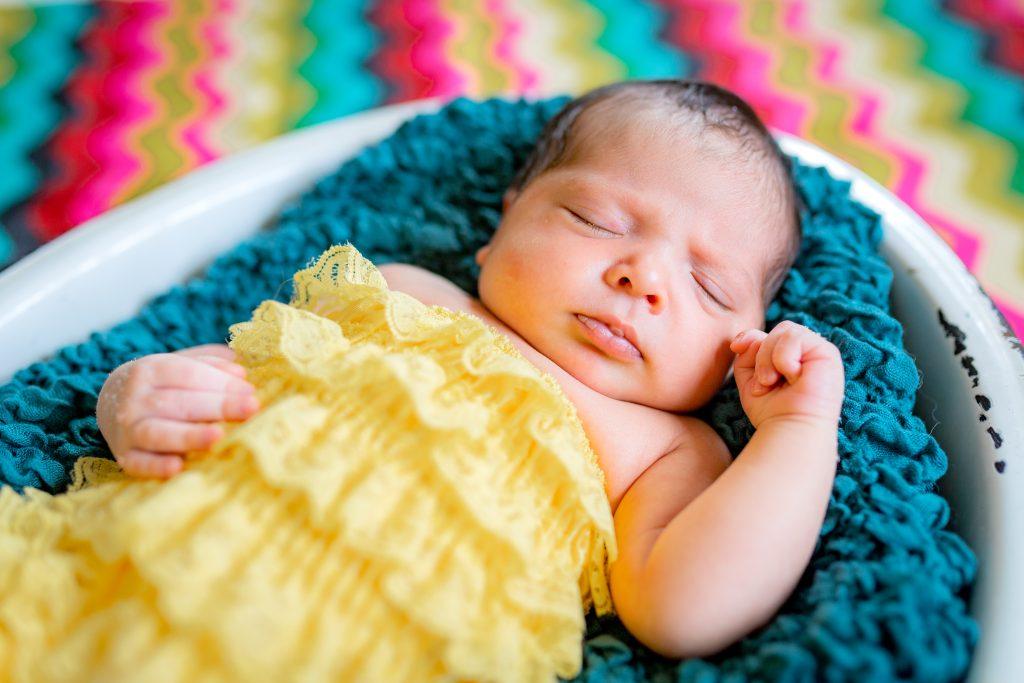 newborn girl snuggled in a bowl