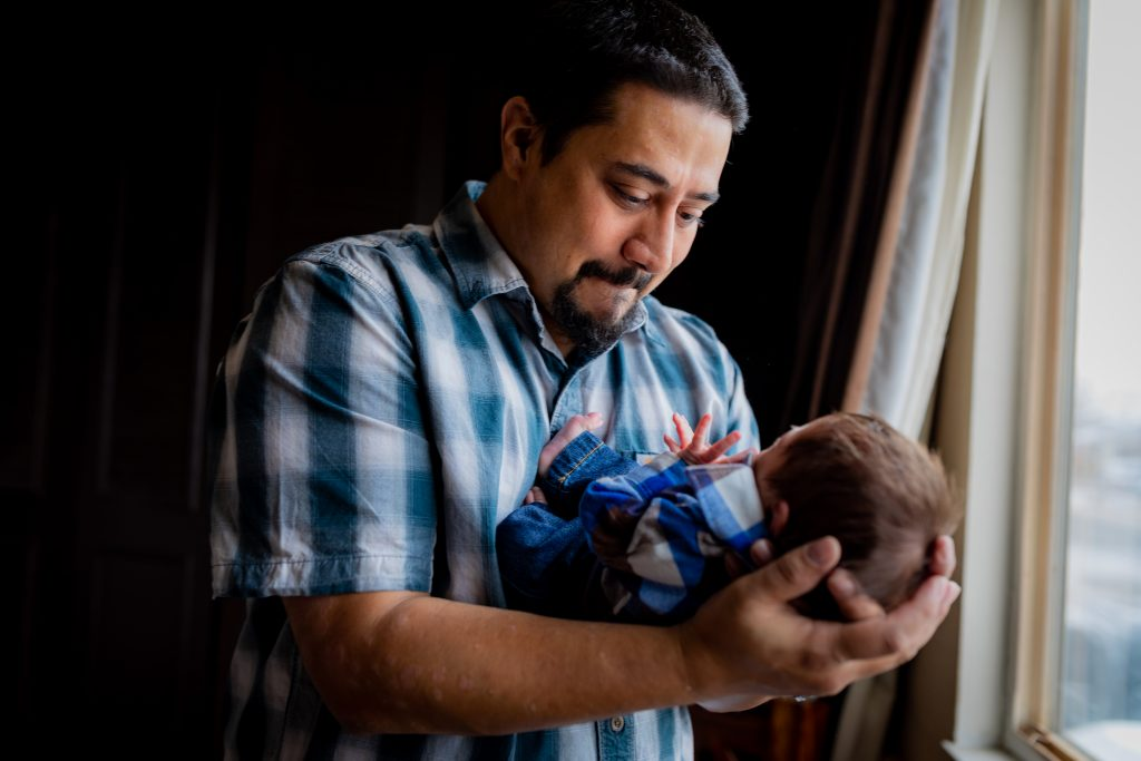 father holding newborn baby in lifestyle session