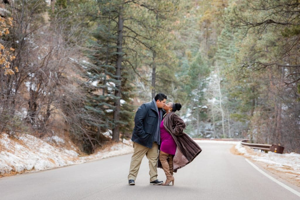 man and woman dressed formally sharing a romantic winter kiss portrait session