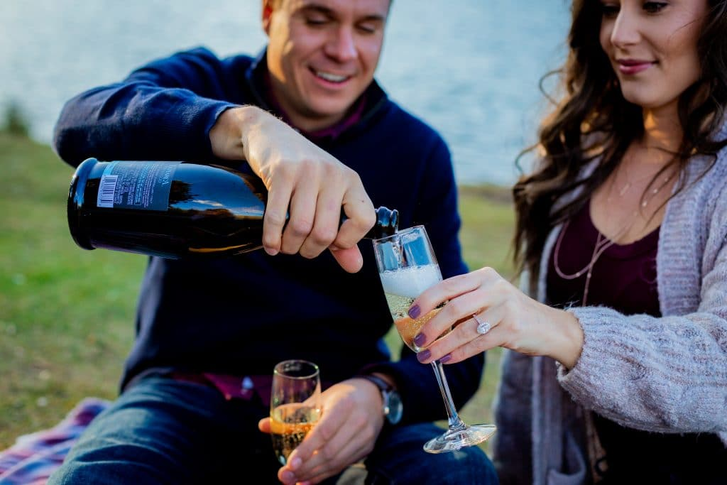 man and woman sharing champagne at engagement portrait session
