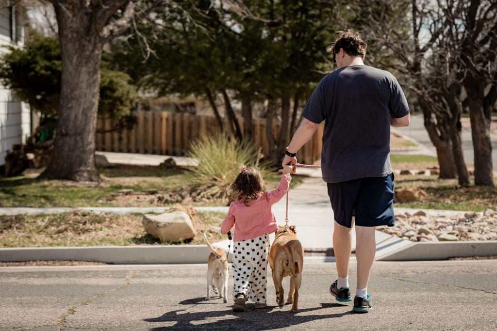 documenting a father and daughter walking together with dogs