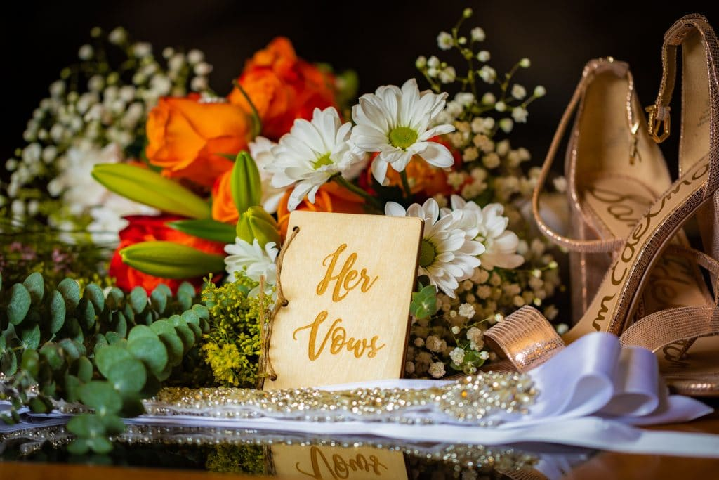 orange and white flowers with brides shoes and vow book