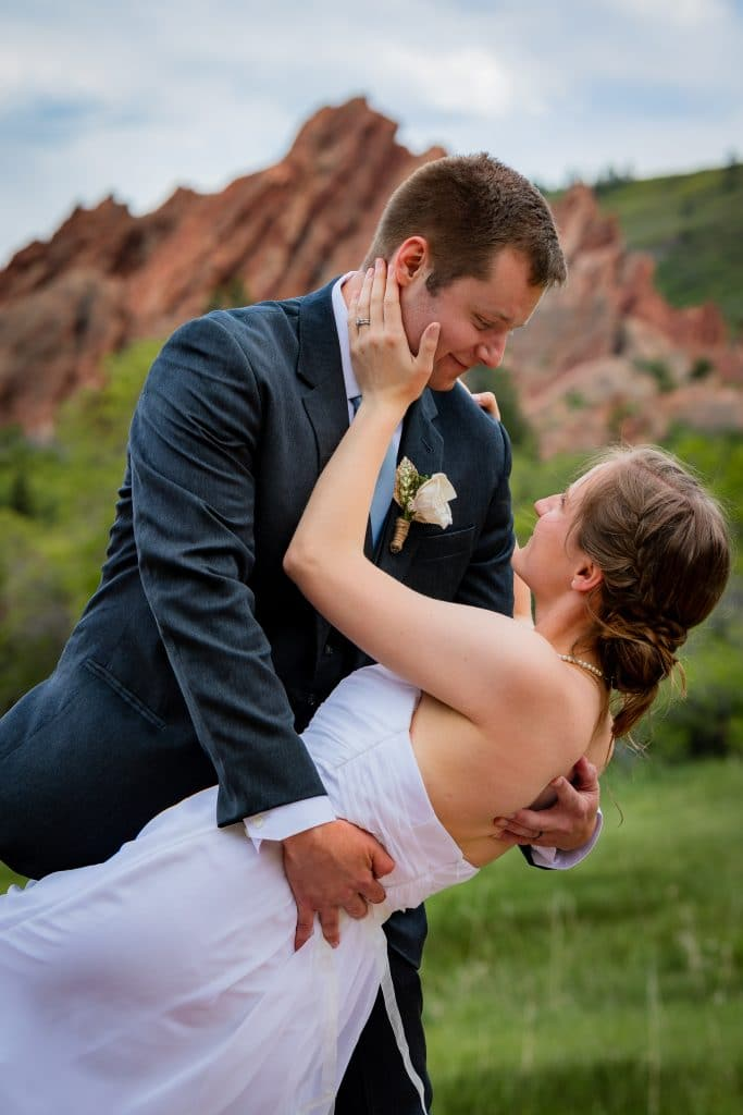 red rocks behind bride and groom