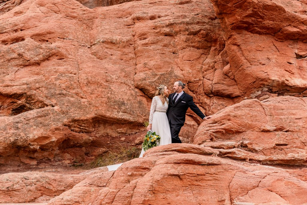 standing in wedding outfits at Garden of the Gods