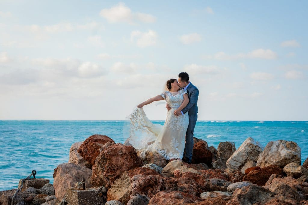 bride and groom kissing on rocks in Jamaica with the ocean behind them