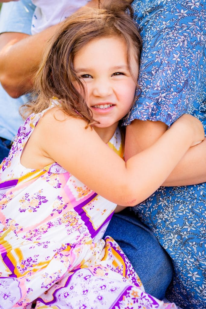 Daughter snuggles mom and smiles big during summer family picture session
