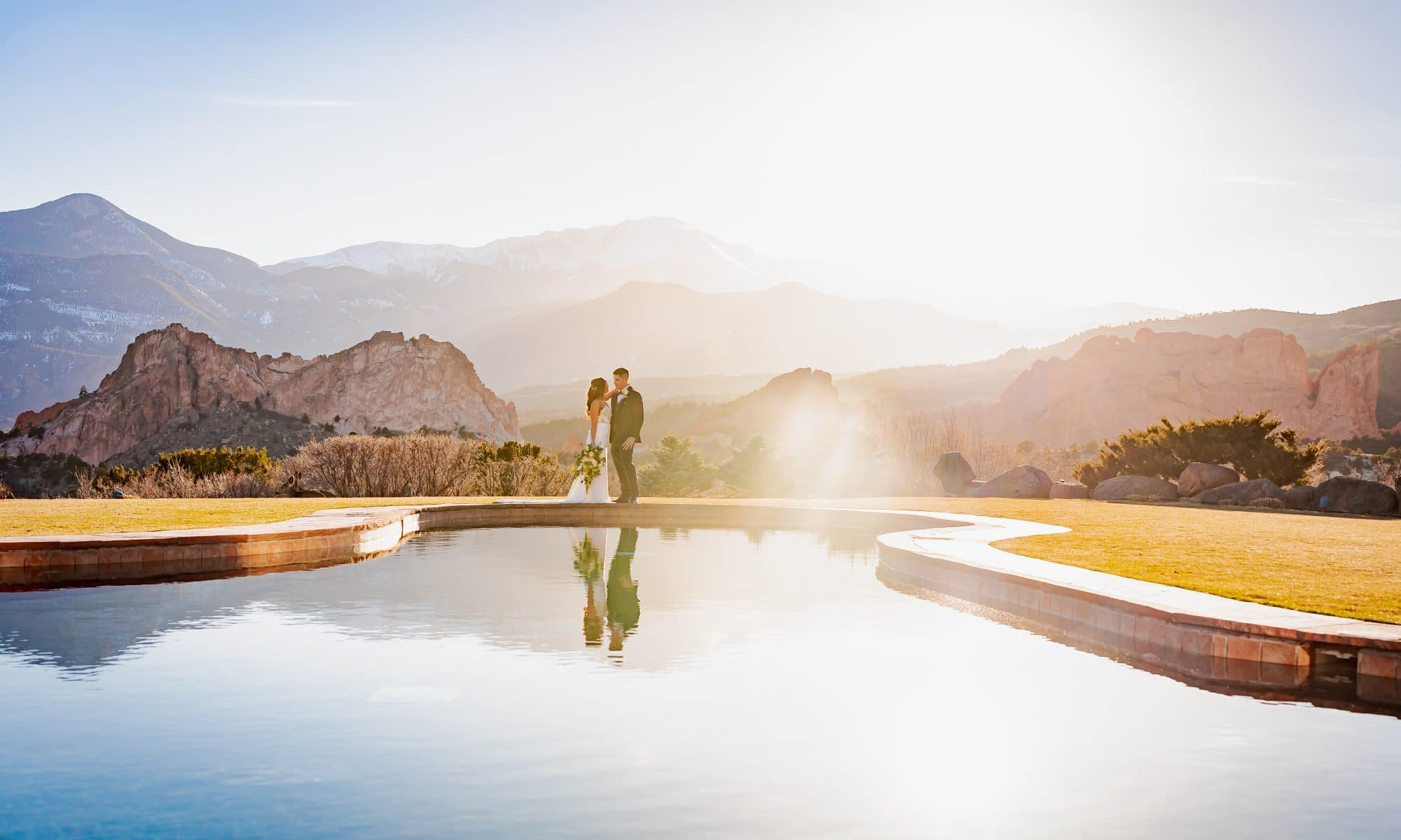 couple on their wedding day at the garden of the gods resort in with their reflection in the pool